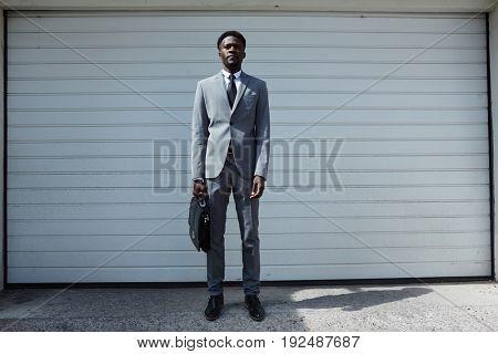 African-american businessman standing by garage door