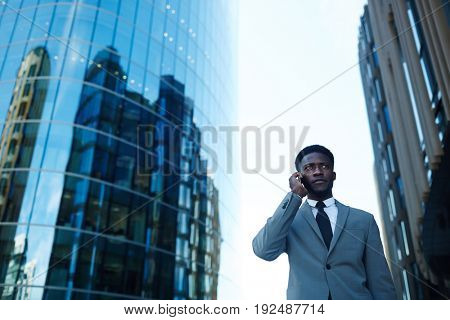 Confident businessman calling on background of skyscrapers
