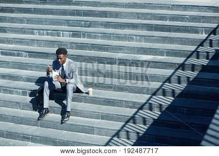 Hungry businessman eating with chopsticks on sunny day