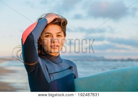 Young beautiful surf girl with long hair and surfboard on beach at sunset or sunrise. Surfer and ocean