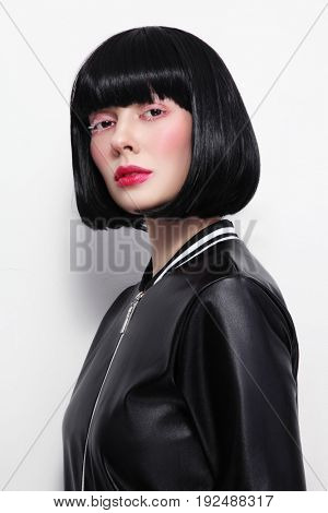 Beautiful brunette with bob haircat and stylish makeup in vintage leather jacket