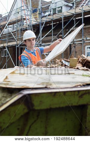 Builder On Site Putting Waste Into Rubbish Skip