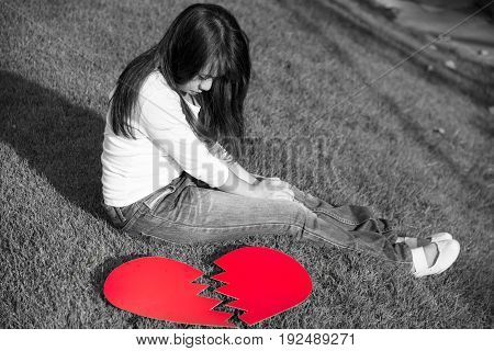 Broken red heart with sad young lady crying on Valentines day fail love concept with black and white tone selective focus