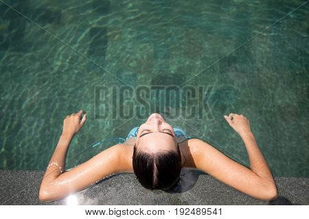 Top view of relaxed young Caucasian woman wearing bikini sitting in swimming pool with closed eyes