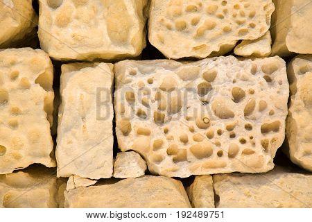 Old wall of porous sand stone bricks, close-up