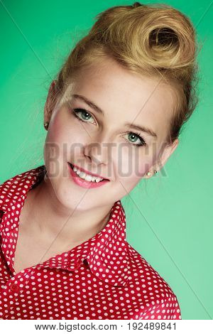 Fashion clothing disguise concept. Lovely young pin up girl in vintage hairstyle wearing retro red shirt. Studio shot on green background