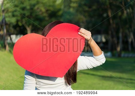 Asian woman holding big red heart shape with space for text decoration over her back on green yard background to show her love on Valentines day concept