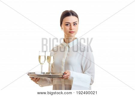 Beautiful waitress with champagne on a trey looking at the camera isolated on white background