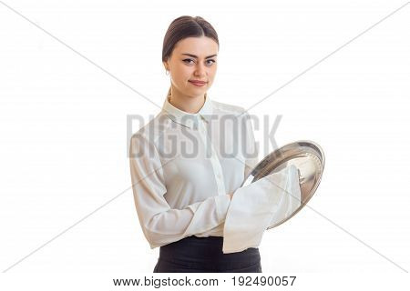 Pretty young waitress cleans a silver trey and looking at the camera isolated on white background