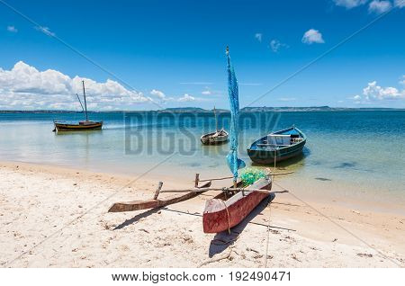 Malagasy outrigger pirogue with sail and boats on the white beach Madagascar