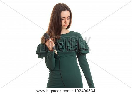 Young womam in green dress holds a microphone in hands isolated on white background