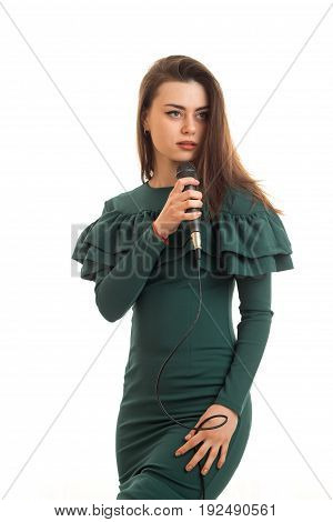 Vertical portrait of beautiful woman in green dress sings a karaoke in microphone isolated on white background