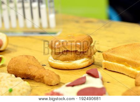 Fast foods (high in fat and carbohydrate) placed on table including pizza burger sandwich and fried chicken. Number of test tubes blurred at background.