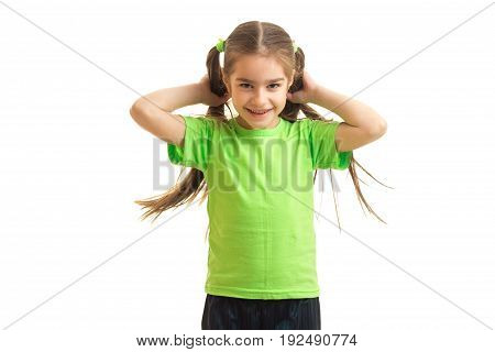 Cheerful little girl in green shirt smiling on holding in hands a horsetail isolated on white background
