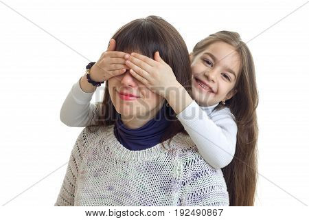 Cheerful girl hides her mothers eyes and smiles isolated on white background