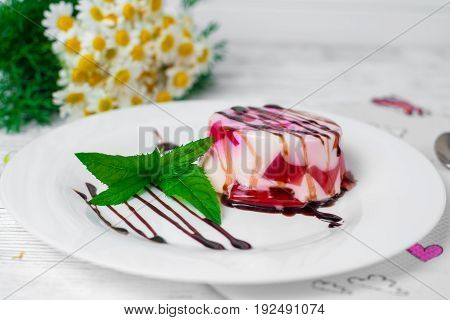 Fruit Jelly With Pieces Of Apricots On A Plate And Spoon On Yellow Knitted Napkin On Old Wooden Tabl