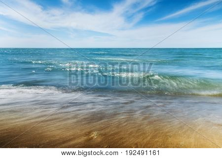 Sunny beach with small waves. Long exposure.