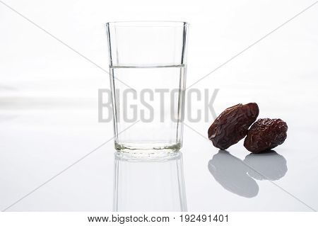 Ramadan ramazan kareem. Traditional glass of water with dry dates for iftar party holidays isolated on white background with copy space. Islamic religion concept.