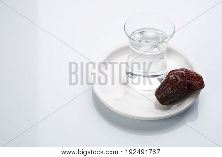 A glass of water and iftar dry dates on white saucer ready to eat for iftar time. Islamic religion and ramadan concept. White background with copy space.