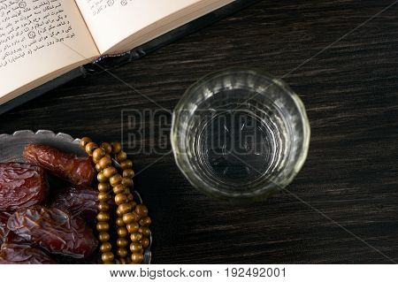 Top view of Silver bowl full of dry dates glass of water for iftar and prayer rosary beads with holy Koran on black background. Ramadan month. Islamic religion concept.