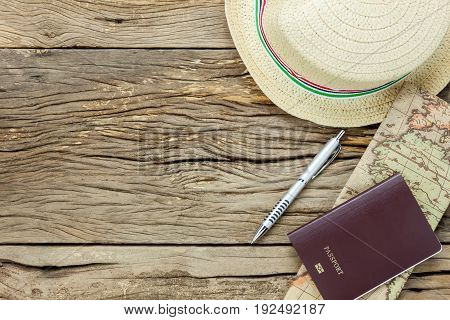 Top view essential items to travel .The map passport pen hat on rustic wooden background.