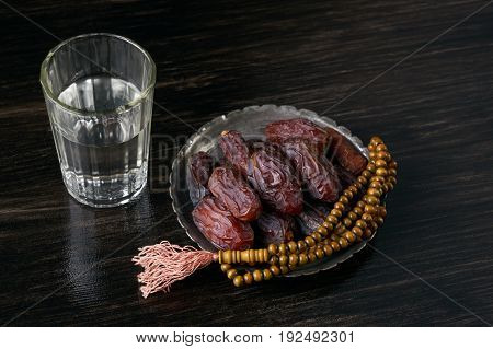 Ramadan kareem with premium dates with prayer rosary beads on silver bowl and glass of water on black wooden table. Islamic religion and iftar holydays month concept.