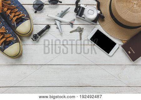 Top view women accessories to travel concept.White mobile phone airplane hat passport watch sunglasses on wood table.