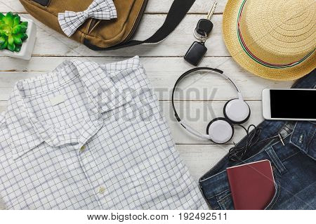 Top view accessoires to travel with man clothing concept.white shirt jean mobile phone listening music by headphone on wooden background.bagpassportkeysunglasses and hat on wood table.