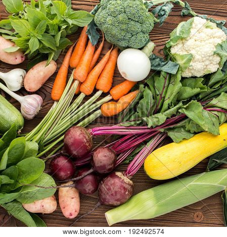 fresh vegetables: beet carrot zucchini broccoli and others on wooden background top view