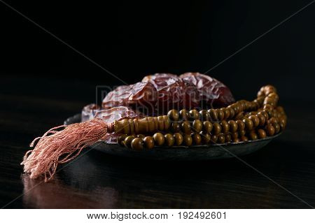 Close-up of Dates for iftar and prayer rosary beads on black wooden table. Islamic religion and ramadan month concept.