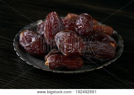 Close-up of Ramadan dates or kurma for iftar opening on silver plate on balck wooden table. Islamic religion and ramadan month concept.