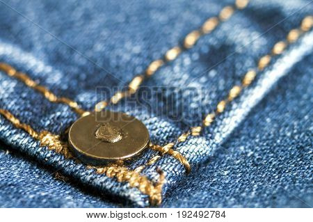 Detail of stud on dark blue jeans close up