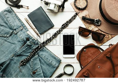 Top view accessories to travel with women clothing concept.White mobile phone watch bag hat map camera necklace trousers and sunglasses on white wood table.