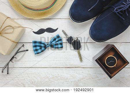 Top view Happy Father day on rustic wooden background. accessories with watch mustache vintage bow tie pen present key car shoes and hat.