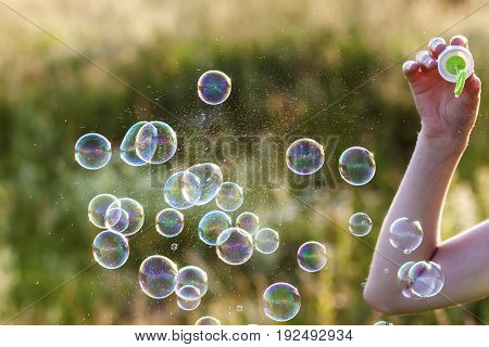 Womans hand with blowing colorful soap bubbles at sunset.