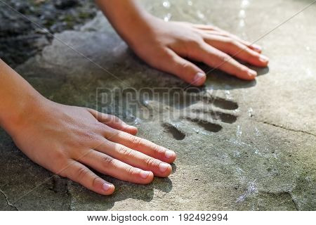 Childs hand and memorable handprint in concrete
