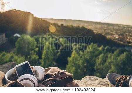 stuff: phone, headphones, backpack. on the peak of the mountain on sunset
