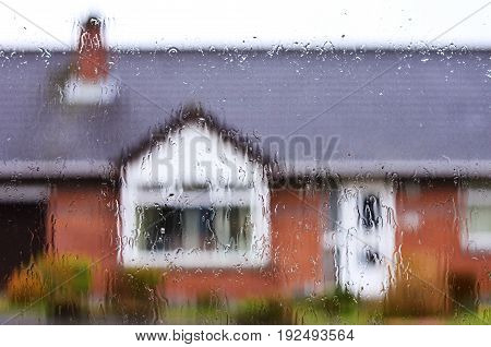 Rain Drops on Glass Window. House Blurred at Background. Raining Scenery.