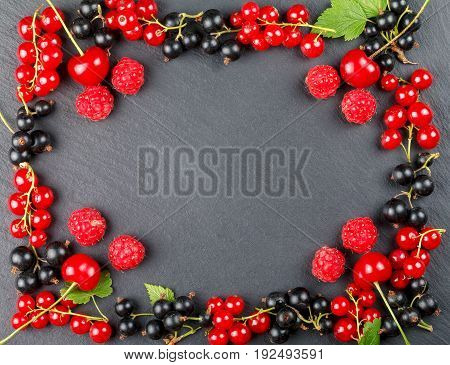 Fresh berries of cherry, raspberries, red currant and blackcurrant on a dark background