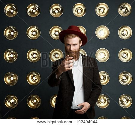 Handsome young redhaired bearded European musician in stylish headwear and dark jacket posing against background of lamps decoration and pointing finger at camera having serious face expression