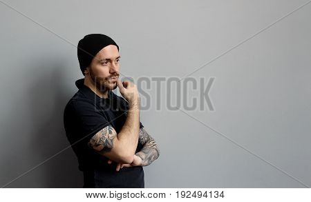 Indoor shot of handsome serious young European man with tattoos touching his beard staring ahead of him having pensive look while thinking over some problem trying to come up with solution