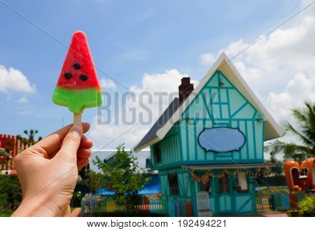 Watermelon shaped ice cream in hand on blue sky and white cloud background. In sunshine day make a feel fresh.