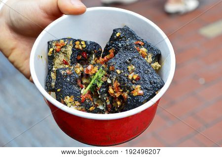 A Hand Holding Black Stinky Tofu. Isolated Blurred Street Background. Stinky Tofu is a Famous Chinese Snack Food.