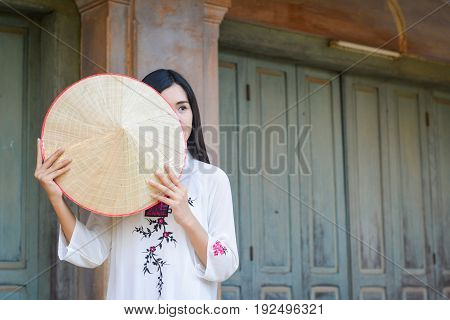 Beautiful women Vietnam with white ao dai dress in old city selective and soft focus of face color vintage style poster