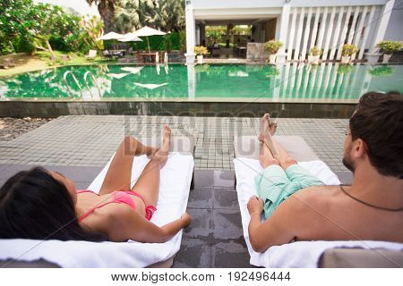 Closeup of young couple lying on chaise longues near swimming pool. They are back to camera.