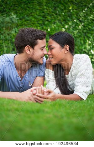 Closeup portrait of smiling young multi-ethnic couple holding hands, touching noses with their eyes closed and lying on patio grass with green leaves wall in background. Front view.