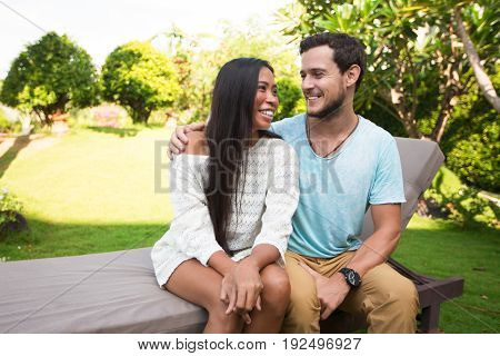 Closeup portrait of smiling young multi-ethnic couple embracing tenderly and sitting on chaise longue with blurred plants in background