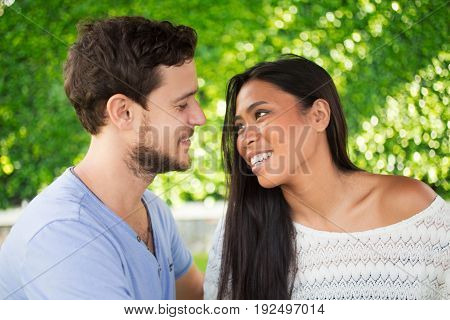 Closeup of smiling young interracial couple looking at each other with blurred green leaves wall in background