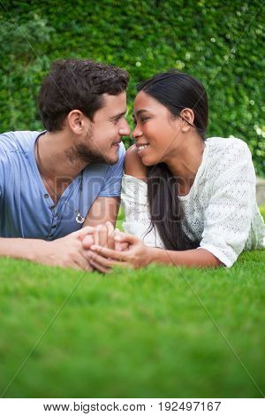 Closeup portrait of smiling young multi-ethnic couple holding hands, looking at each other and lying on patio grass with green leaves wall in background. Front view.