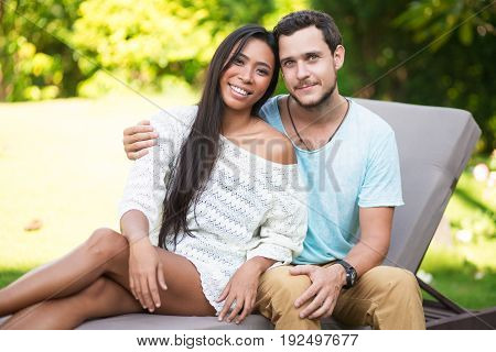 Closeup portrait of smiling young Caucasian man embracing Asian girlfriend. They are looking at camera and sitting on chaise longue with blurred trees in background. Front view.